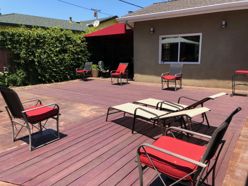 Back yard with wooden deck and chairs.