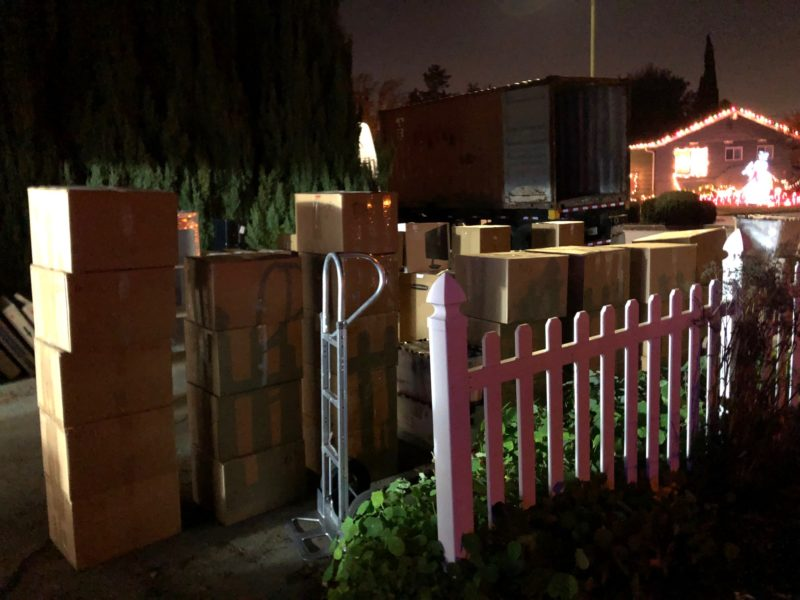 boxes piled in the driveway, container truck and Christmas lights in the background