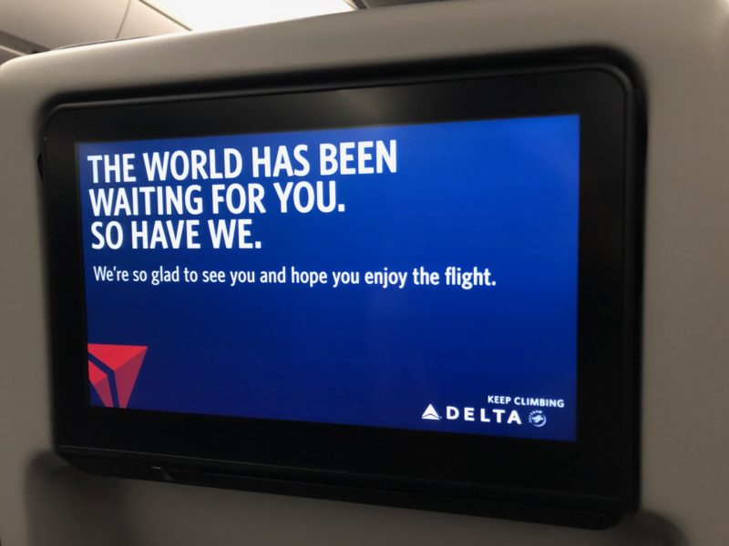 "sign on Delta's in-flight entertainment system saying ""The world has been waiting for you. So have we."""
