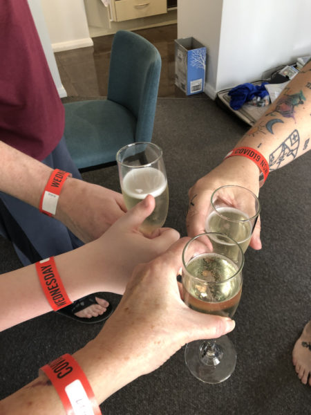 4 arms with wristbands, 3 of them holding glasses of prosecco, one child's hand giving a thumbs up