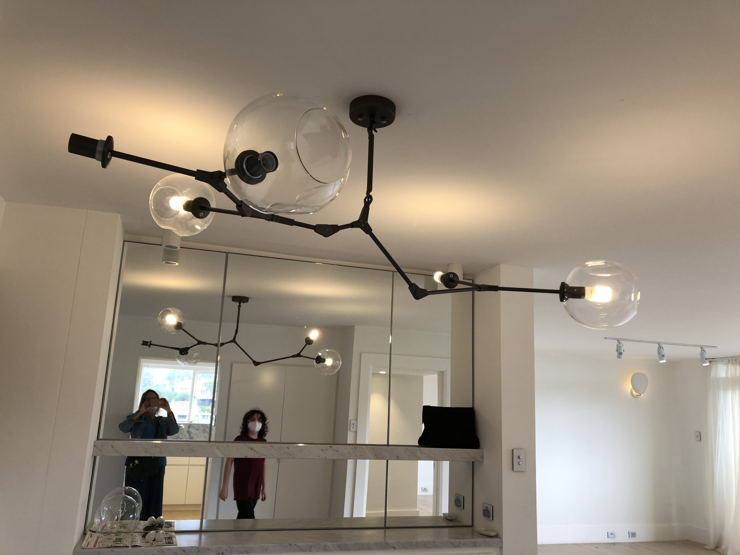 Deirdré and Mitchell reflected in a mirror, with a large weird light fixture overhead