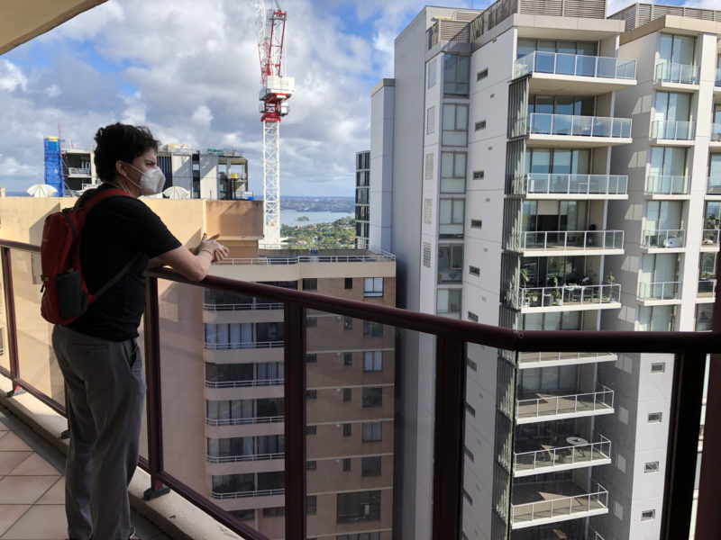 Brendan looking from a balcony high up, with other tall buildings and a crane in the background