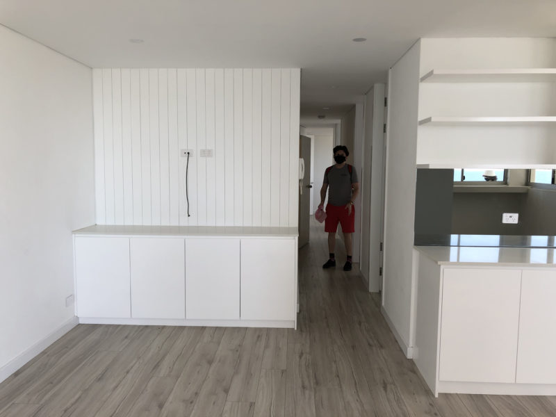 Brendan seen down a hallway, white cabinets and kitchen area in the foreground