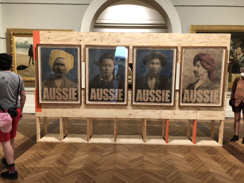 "artwork: four posters showing antique photographs of people Chinese and Indian descent, each labeled ""Aussie"""