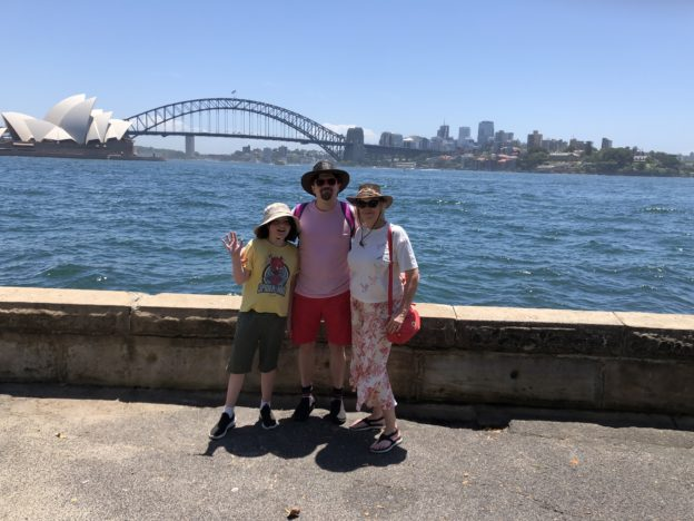 Mitchell, Brendan, and Deirdré in front of a view of the Sydney Harbour Bridge